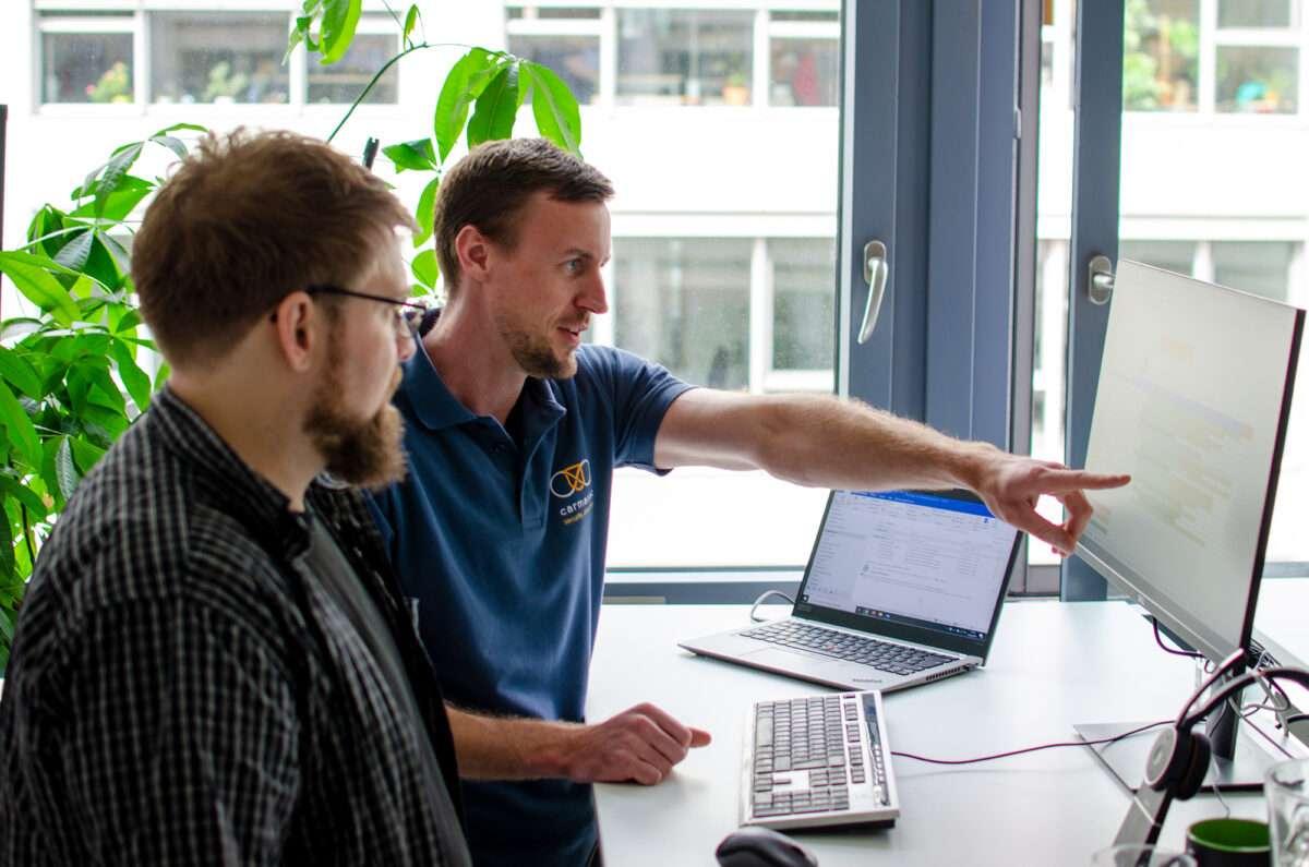 Jan Sudmeyer, Geschäftsführer der carmasec, erläutert Security Consultant Simon Decker einen Projektplan