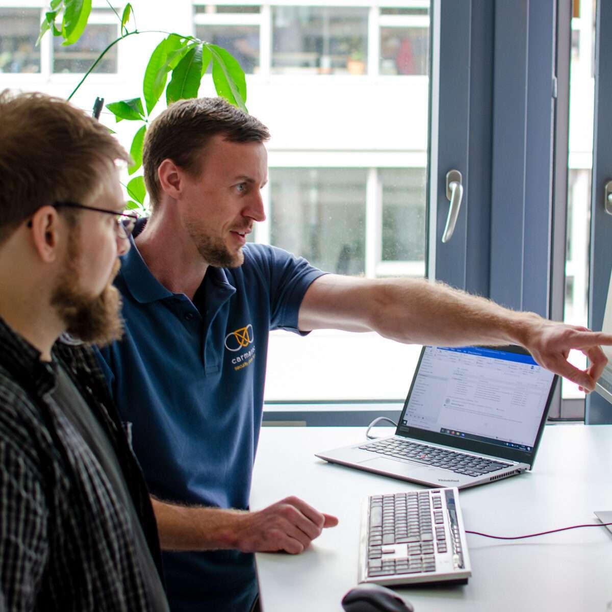 Geschäftsführer Jan Sudmeyer erläutert Security Consultant Simon Decker einen Projektplan